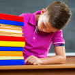 Adorable schoolboy with stack of books — Stock Photo