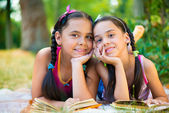 Portrait of two hispanic sisters reading in the park — Stock Photo