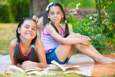 Happy hispanic sisters reading in the park — Stock Photo