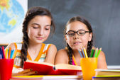 Portrait of two beautiful schoolgirl in classroom — Stock Photo
