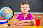 Cute diligent boy sitting in classroom — Stock Photo