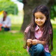 Cute hispanic girl in park with mother on background — Stock Photo