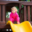 Curly blonde girl sliding at playground — Stock Photo