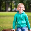 Cute little boy sitting on bench — Stock Photo
