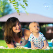 Young mother and little son looking at soap bubbles — Stock Photo #32826677
