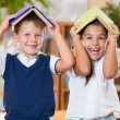 Two happy schoolchildren have fun in classroom — Stok fotoğraf