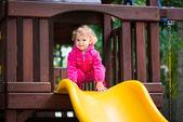 Curly blonde girl sliding at playground — Stock Photo