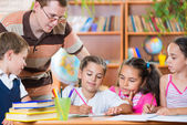 Portrait of diligent schoolkids and their teacher — Stock Photo