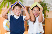 Two happy schoolchildren have fun in classroom — Foto Stock
