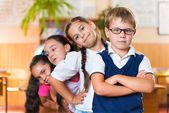 Four adorable schoolchildren standing in classroom — Stock Photo