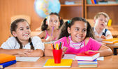 Happy schoolchildren during lesson in classroom — Stock Photo