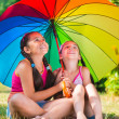 Happy sisters under colorful umbrella in park — Stok fotoğraf
