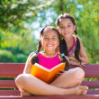 Happy hispanic sisters reading book in summer park — Stock Photo