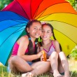 Happy sisters under colorful umbrella in park — Stock Photo