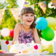 Pretty girl with cake at birthday party — Stockfoto