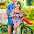 Two happy children sitting on bicycle — Stock Photo