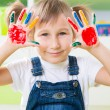 Happy little girl with colorful pains on hands — ストック写真