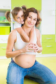 Happy pregnant mother with daughter — Stock Photo