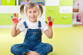 Happy little girl with colorful pains on hands — Stock Photo