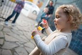 Cute little girl blowing soap bubbles — Stock Photo