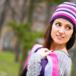 Beautiful young girl in striped hat — Stock Photo