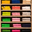 Colour shirts at shelf in shop — Stock Photo
