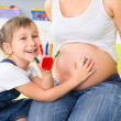 Llittle girl painting on pregnant belly — Stockfoto #39558713