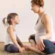 Pregnant woman and little daughter yoga exercising — Stock Photo