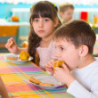Children eating baked apple and cookie at daycare — Stock Photo #43955975