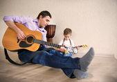 Padre de joven y pequeño hijo tocando la guitarra — Foto de Stock