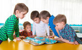 Cute preschoolers plaing game on table — Stock Photo
