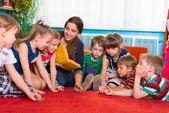 Reading to children at kindergarten — Stock Photo