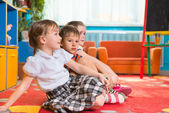 Cute preschoolers sitting on floor and listening — Stock Photo