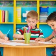 Three preschool children drawing at daycare — Stock Photo #46642011