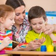 Cute children drawing with teacher at preschool class — Stock Photo #46644149