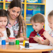 Cute children drawing with teacher at preschool class — Stock Photo #46644523