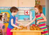 Two little girls playing in checkers at kindergarten — Stock Photo