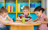 Three preschool children drawing at daycare — Stock Photo