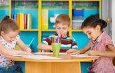 Three preschool children drawing at daycare — Stock Photo