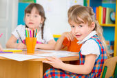 Two little girls drawing at kindergarten — Stock Photo