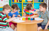 Cute children drawing with colorful paints at kindergarten — Stock Photo
