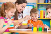 Cute children drawing with teacher at preschool class — Stok fotoğraf