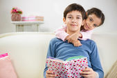 Two children reading book at home — Stock Photo