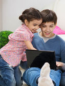 Excited bother and sister with laptop — Stock Photo