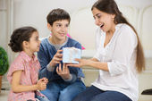 Cute children presenting a gift to mother — Stock Photo