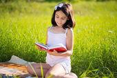 Happy child studying on nature — Stock Photo