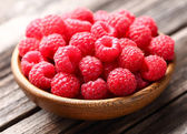 Fresh raspberry in a wooden plate — Stock Photo