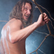 Screaming long haired naked man in the forest - Stock Photo