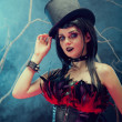 Attractive smiling gothic girl in tophat and feather corset — Stock Photo