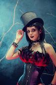 Attractive smiling gothic girl in tophat and feather corset — Zdjęcie stockowe
